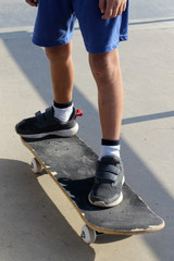 Feet of a kid who is standing on a skateboard in a skate park