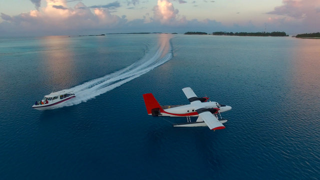 Aerial photo of seaplane during sunset. White black red seaplane docked in the middle of the Maldivian lagoon of Indian Ocean, far away from Island. Speed boat is passing by