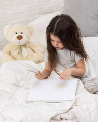 cute little girl with teddy bear drawing pictures while lying on bed. Kid painting at home