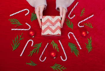 Woman holding Christmas presents on a Red table background.