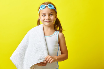 Beautiful little girl in swimsuit and swimming glasses standing on yellow isolated background.