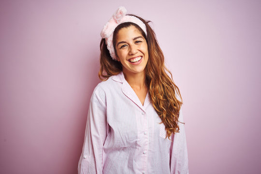 Young beautiful woman wearing pajama standing over pink isolated background with a happy and cool smile on face. Lucky person.