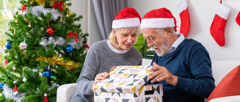 Senior couple husband and wife opening gift present box, sitting on sofa in room with Christmas tree and decoration