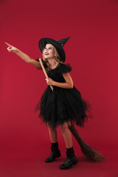 Pleased little girl witch in carnival halloween costume