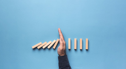 Chain Reaction In Business Concept, Businessman Intervening Chain Dominoes Toppling