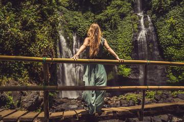 Woman in turquoise dress at the Sekumpul waterfalls in jungles on Bali island, Indonesia. Bali...