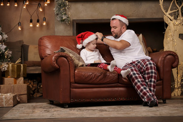 Picture of father in Santa hat and son on red sofa in room