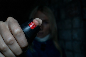 Blonde woman holding pepper spray for self defense close up