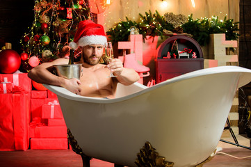 New year. Holidays celebration. Party for adults. Naughty Santa concept. Bad Santa Claus lying in bathtub over christmas tree interior background. Attractive man Santa hat drinking champagne alcohol
