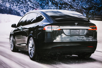 Berlin, December 12, 2017: Photo of the image of an electric vehicle Tesla model X at the Tesla motor show in Berlin. A modern electric car. The picture shows a car on a winter road.