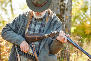 Hunter male loading gun, wearing casual hunting clothes, stock and knife on lower back. Forest background