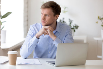Pensive businessman distracted from job looking away.