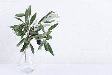 Foto op Aluminium Olijfboom green olive branches in glass vase on a white brick wall background. Wall mockup. Minimal home decor. Simple modern interior design