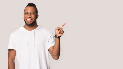 Smiling biracial man in glasses point at blank copy space