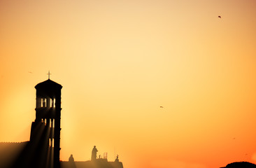 Poster - Silhouettes of the bell tower and statues of figures of people on the rooftops of Rome against the backdrop of the sunset sky.  Rome. Italy. Europe.
