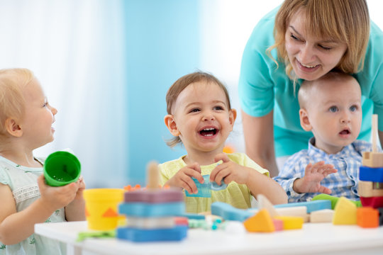 Babies play with teacher in nursery or creche