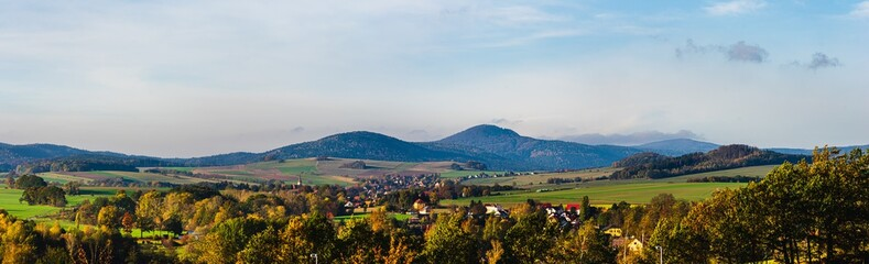 panoramic autumn view on Lusatian Mountains with the villages Hoernitz and Bertsdorf in the foreground and Mount Lausche in the background as seen from Zittau