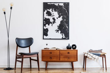 Stylish and retro living room with design vintage wooden commode, chair, footrest, black lamp and...