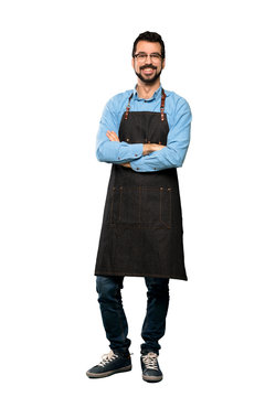 Full-length shot of Man with apron with glasses and happy over isolated white background