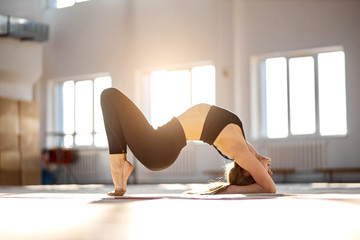 Attractive pretty female gymnast in black sportswear, leggings and bra, beautiful girl doing exercise, working out at professional studio