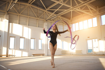 Tall fit art gymnast dancing in big bright sports hall, holds colourful ribbon in hand, looks aside with confident expression, side shot, big sport concept