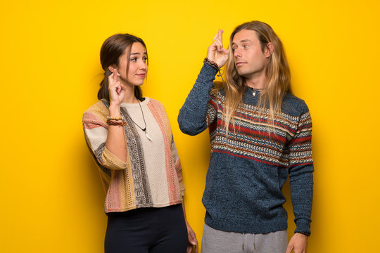 Hippie couple over yellow background with fingers crossing and wishing the best