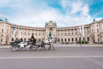 Spoed Fotobehang Wenen Hofburg Palace and Heldenplatz with a passing carriage with a pair of horses, Vienna, Austria