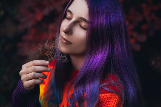 Teenager with violet hair in colorful sweater.