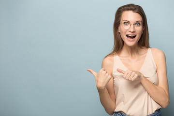 Excited millennial woman point at blank copy space