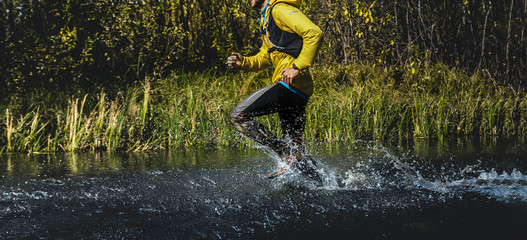 Fototapete - man runner with camelbak run marathon river crossing