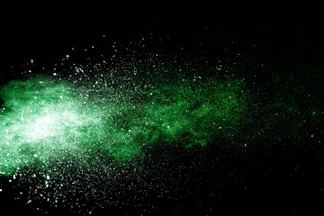 Green powder explosion on black background.