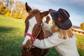 Woman with cowboy hat is hugging her young horse at pasture