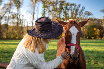 Woman with cowboy hat is talking her young horse at farm