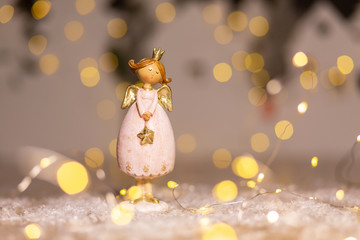 Decorative Christmas-themed figurines. Statuette of a Christmas angel. Christmas tree decoration. Festive decor, warm bokeh lights.
