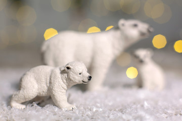 Foto op Plexiglas Ijsbeer Decorative figurines of a Christmas theme. Statuettes of a family of polar bears. Christmas tree decoration. Festive decor, warm bokeh lights.