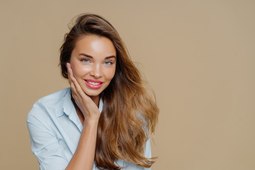 Portrait of cheerful smiling woman touches cheek, has toothy charming smile, wears shirt, looks at camera with pleasure, has long wavy hair, makeup, poses against brown background, free space
