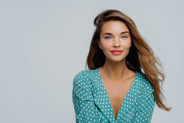 Studio shot of positive young woman has long wavy hair, makeup, wears turquoise polkadot blouse, looks straightly at camera, models against white background, copy space for your advertisement