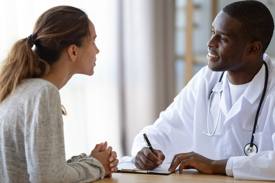 African American male doctor consulting female patient
