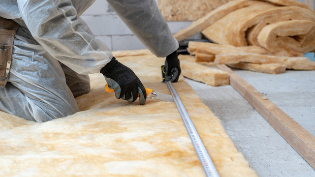 Professional workman installing thermal insulation rock wool under the roof