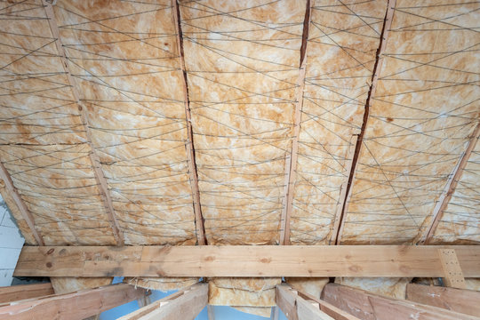 House under construction with insulation glass wool on an attic floor