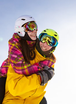Young happy couple in snowy mountains. Winter sport vacation. activity holiday concept. the girl hugs the guy and they are in ski helmets, masks and bright clothes. clean background and edit space