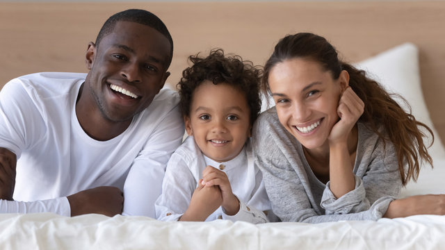 Portrait of happy multiracial family of three posing in bedroom