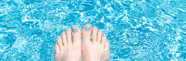 Foto op Plexiglas Pedicure Female feet with glitter pedicure under clear pool water, banner.