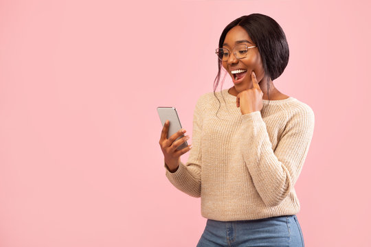 Excited Girl Using Smartphone Holding Finger On Chin, Pink Background