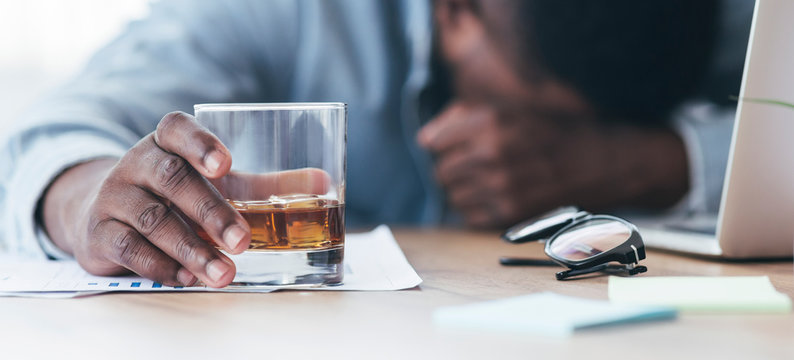 Drunk black employee sleeping at workplace, holding glass with alcohol