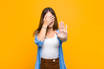 young pretty woman covering face with hand and putting other hand up front to stop camera, refusing photos or pictures against orange wall