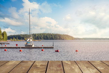 Yacht near the wooden mini pier on Lake in Finland. On a summer evening