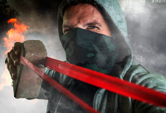 young man as ultra and radical anarchist rioter . furious antifa protester in face mask throwing brick hostile on street on demonstration in violet riot and chaos
