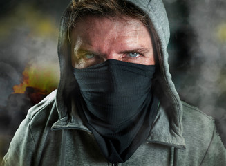 young man as ultra and radical anarchist rioter . furious antifa protester in face mask hostile on street on demonstration in violet riot and chaos between fire and smoke
