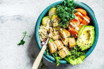 Fototapeta Buddha bowl with quinoa, tofu, avocado, sweet potato, brussels sprouts and tahini dressing, top view. Healthy vegan food concept. obraz